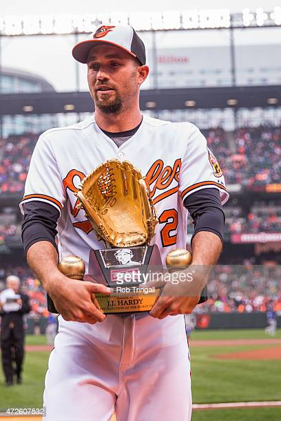 J Hardy of the Baltimore Orioles receives his Gold Glove Trophy before the game against the Toronto Blue Jays at Oriole Park at Camden Yards on...