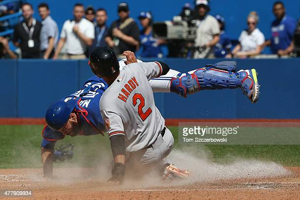 J Hardy of the Baltimore Orioles slides into home plate to score a run in the ninth inning during MLB game action as Russell Martin of the Toronto...