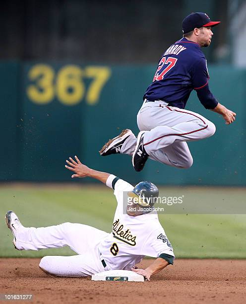 J Hardy of the Minnesota Twins leaps over Kurt Suzuki of the Oakland Athletics on a double play hit by Jack Cust in the fourth inning during an MLB...