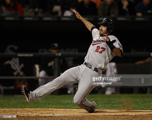 J Hardy of the Minnesota Twins slides into the plate to score a run against the Chicago White Sox at US Cellular Field on September 14 2010 in...