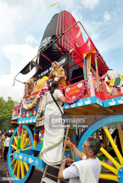 A Hare Krishna climbs aboard a giant decorative wheeled shrine before being pulled by hand from Hyde Park to Trafalgar Square to celebrate the...