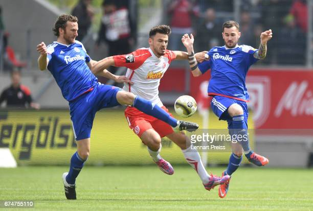 Haris Hyseni of Jahn Regensburg challenges Dominic Peitz and Dominik Schmidt of Holstein Kiel during the 3 Liga match between Jahn Regensburg and...
