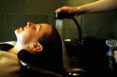 Hari's salon employee has her hair rinsed after application of the bull semen and katera treatment at Hari's Salon on February 6 2007 in London...