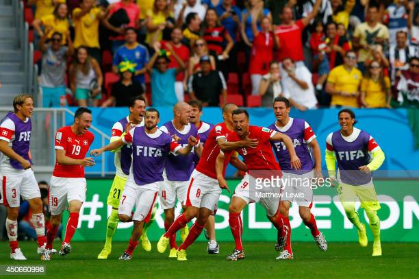 Haris Seferovic of Switzerland celebrates scoring his team's second goal with teammates during the 2014 FIFA World Cup Brazil Group E match between...
