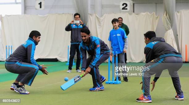 Haris Sohail Hasan Ali and Shadab Khan of Pakistan play cricket with local school children during an ICC Champions Trophy Cricket for Good clinic at...