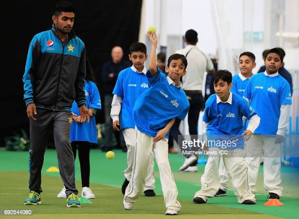 Haris Sohail of Pakistan shows a young school child how to bowl during an ICC Champions Trophy Cricket for Good clinic at Edgbaston on June 5 2017 in...