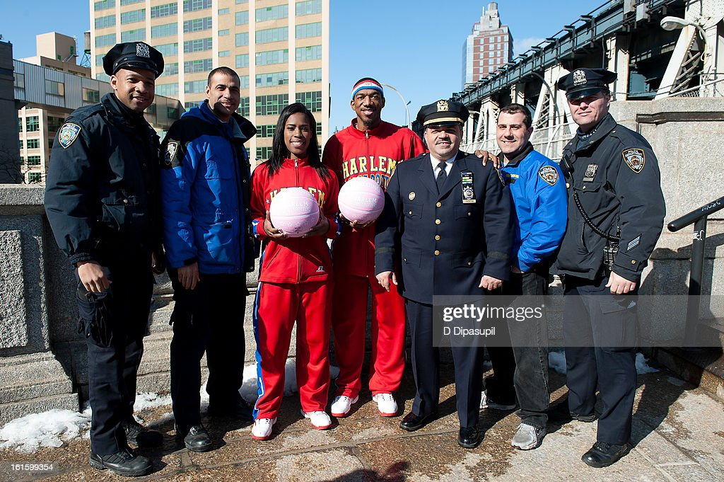 Harlem Globe Trotters Fatima 'TNT' Maddox (3rd L) and Anthony 'Buckets' Blakes (C) pose with members of the New York City Police Department at the Manhattan Bridge on February 12, 2013 in New York City.