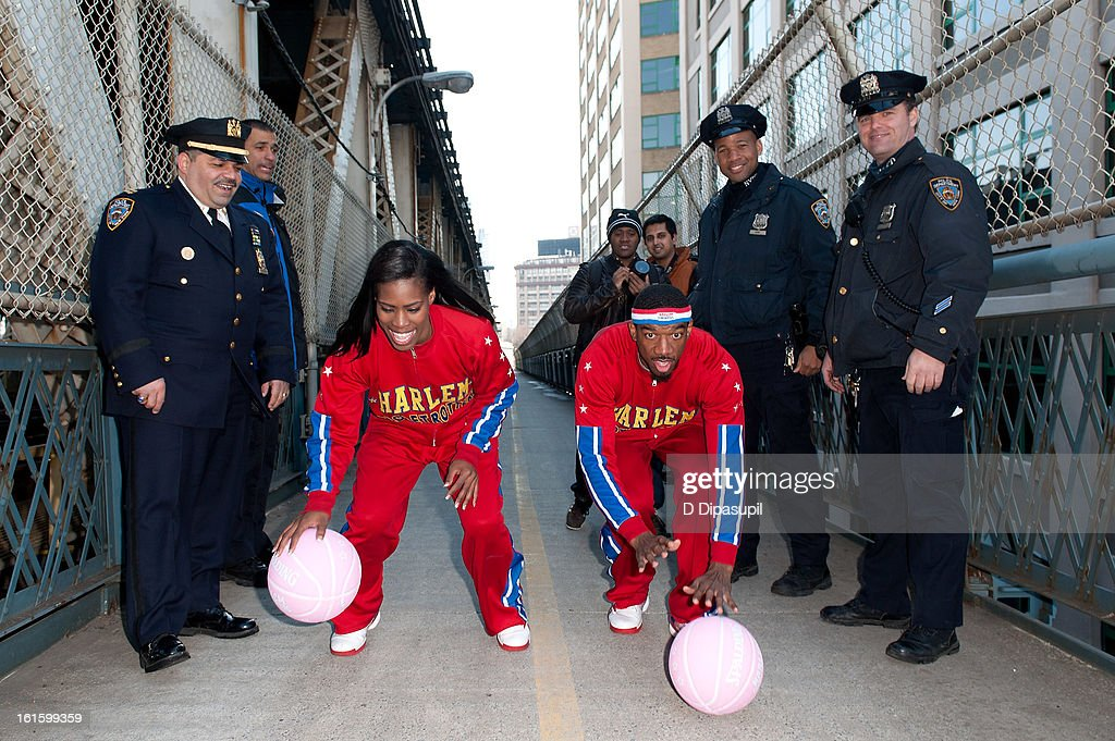 Harlem Globe Trotters Fatima 'TNT' Maddox (L) and Anthony 'Buckets' Blakes (R) dribble from Brooklyn to Manhattan at the Manhattan Bridge on February 12, 2013 in New York City.