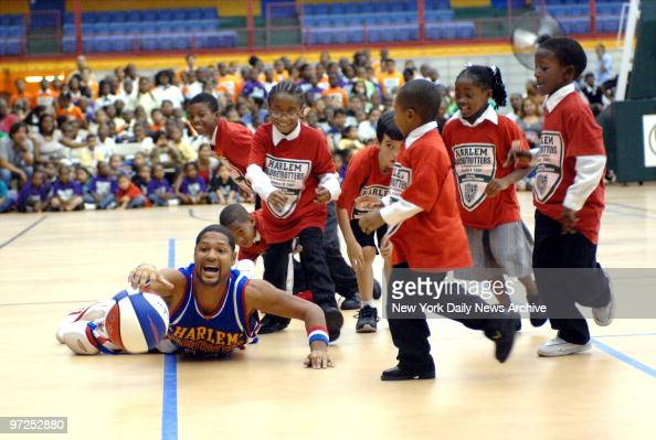 Harlem Globetrotters' Chris Franklin battles a group of children from the Police Athletic League for the ball at the Harlem Armory Center as the...