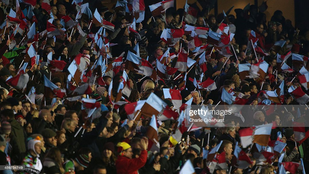 Harlequins fans wave their flags during the Aviva Premiership match between Harlequins and Exeter Chiefs at Twickenham Stadium on December 28, 2013 in London, England.