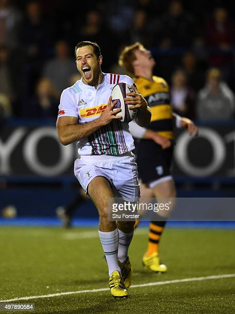 Harlequins wing Tim Visser celebrates as he races through to score as Rhys Patchell of the Blues reacts in the background during the European Rugby...