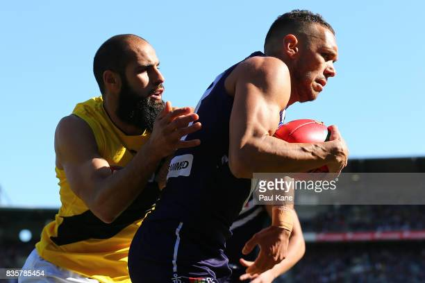 Harley Bennell of the Dockers gets taken over the line by Bachar Houli of the Tigers during the round 22 AFL match between the Fremantle Dockers and...