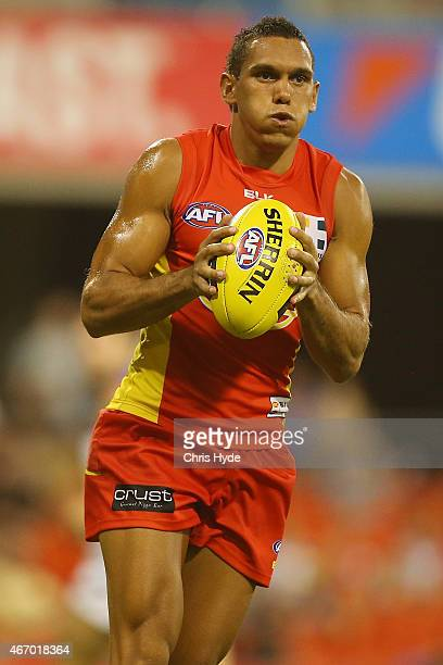 Harley Bennell of the Suns runs the ball during the NAB Challenge AFL match between the Gold Coast Suns and the Brisbane Lions at Metricon Stadium on...