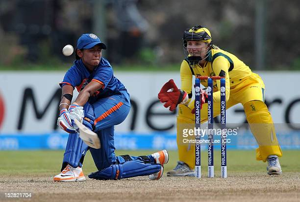 Harmanpreet Kaur of India sweeps the ball away as Jodie Fields of Australia stands by the stumps during the ICC Women's World Twenty20 Group A match...