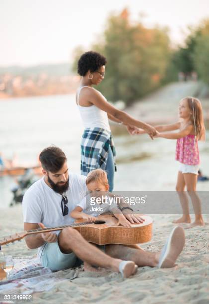 Harmonious family: boys are playing guitar, girls are dancing