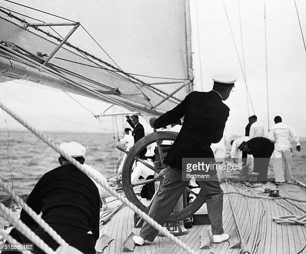 Harold S Vanderbilt at the wheel of his yacht Ranger as he prepares to defend the America's Cup | Location Off Newport Rhode Island USA