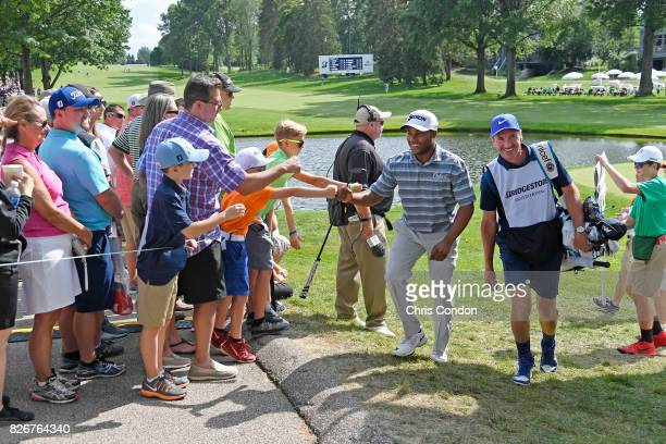 Harold Varner III high fives fans during the third round of the World Golf Championships Bridgestone Invitational at Firestone Country Club South...