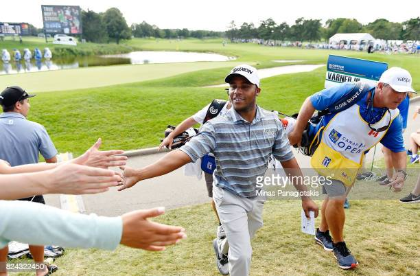 Harold Varner III of the United States greets fans as he exits the 18th green during the third round of the RBC Canadian Open at Glen Abbey Golf Club...