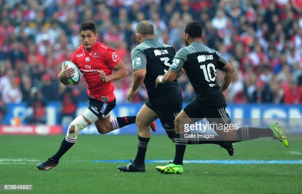 Harold Voster of Lions is tackled by Richie Mounga and Jack Goodhue of Crusaders during the Super Rugby Final match between Emirates Lions and...