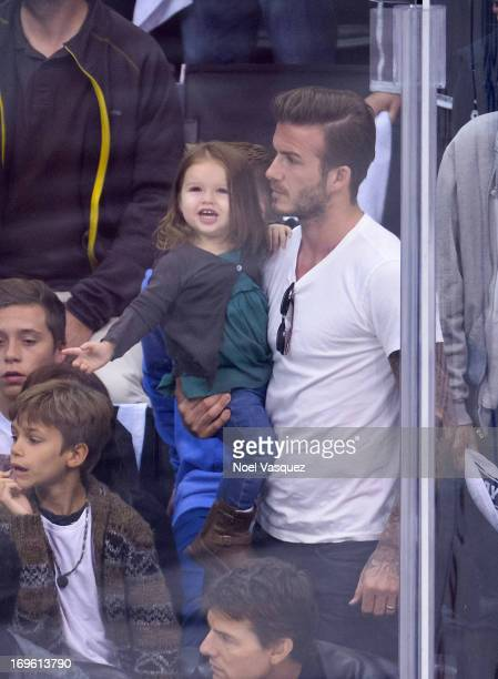 Harper Beckham and David Beckham attend an NHL playoff game between the San Jose Sharks and the Los Angeles Kings at Staples Center on May 28 2013 in...