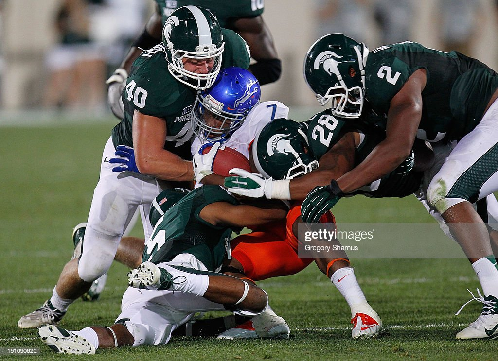 D.J. Harper #7 of the Boise State Broncos is tackled during a third quarter run by Max Bullough #40, Johnny Adams #5, Denicos Allen #28 and William Gholston #2 of the Michigan State Spartans at Spartan Stadium on August, 2010 in East Lansing, Michigan.