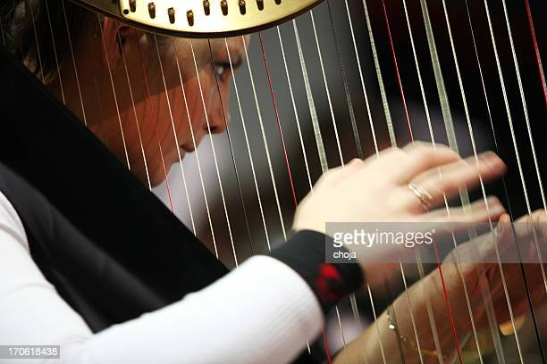 Harpist playing at concert...orchestra in the back