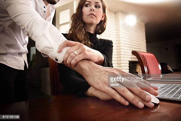 Harrassed woman removing his hand. She wears ring.