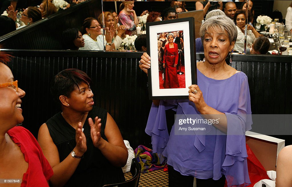 Harriette Cole and Agnes Cammock watch as Ruby Dee opens gifts at a celebration of Ruby Dee's style at Melba's restaurant on June 9, 2008 in New York City.