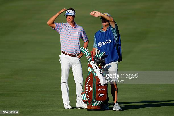 Harris English of the United States waits on the tenth fairway alongside caddie Brian Smith during the first round of the 2016 PGA Championship at...