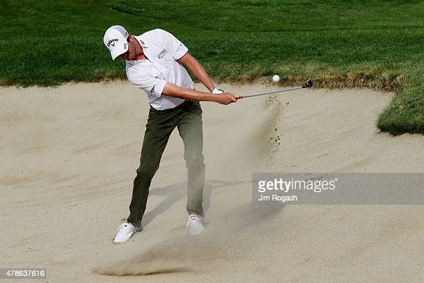 Harris English plays a shot from a bunker on the 11th hole during the second round of the Travelers Championship at TPC River Highlands on June 26...