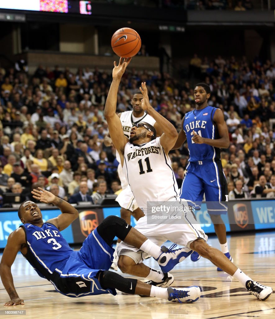 J Harris of the Wake Forest Demon Deacons runs into Tyler Thornton of the Duke Blue Devils as he drives to the basket during their game at Lawrence...