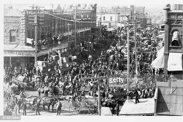 Harrison Avenue is crowded with people and loaded wagons during the peak of trading at the Guthrie Cotton Market Guthrie Oklahoma Territory ca 1893