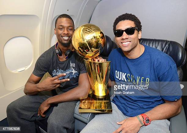 Harrison Barnes and James Michael McAdoo of the Golden State Warriors hold the NBA trophy on the plane as the team travels home from Cleveland after...