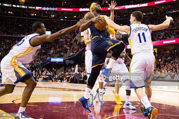 Harrison Barnes and Klay Thompson of the Golden State Warriors try to stop LeBron James of the Cleveland Cavaliers during the second half at Quicken...