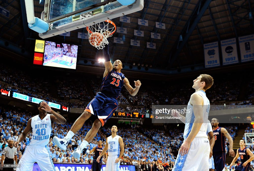 Harrison Barnes and Tyler Zeller of the North Carolina Tar Heels watch as Akil Mitchell of the Virginia Cavaliers dunks during play at the Dean Smith...