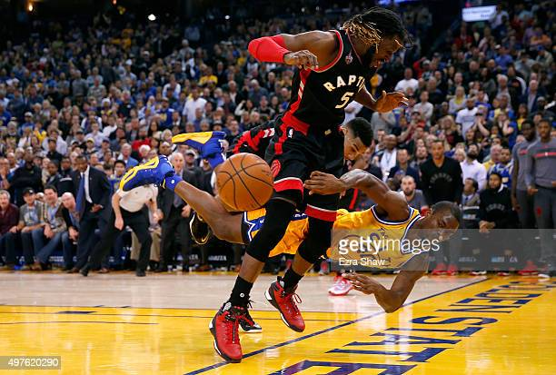 Harrison Barnes of the Golden State Warriors dives to save the ball from going out of bounds as DeMarre Carroll of the Toronto Raptors looks on at...