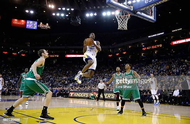 Harrison Barnes of the Golden State Warriors gets a rebound and puts it back in for a basket while Tyler Zeller James Young and Phil Pressey of the...