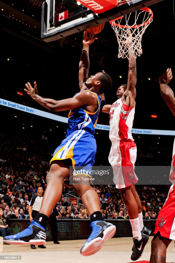 Harrison Barnes #40 of the Golden State Warriors shoots a reverse layup against Ed Davis #32 of the Toronto Raptors on January 28, 2013 at the Air Canada Centre in Toronto, Ontario, Canada.