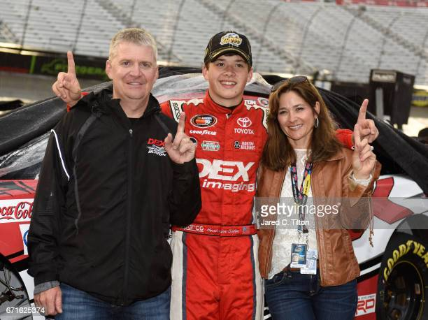 Harrison Burton driver of the Dex Imaging Toyota poses for a photo with his father Jeff Burton and mother Kim Burton after winning the NASCAR KN Pro...