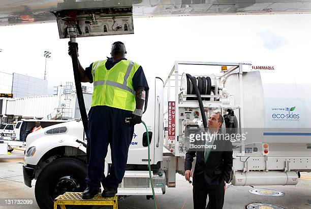 Harrison Dillon president and chief technology officer of Solazyme Inc right watches a worker fuel a Boeing 737800 bearing the Eco Skies livery at...
