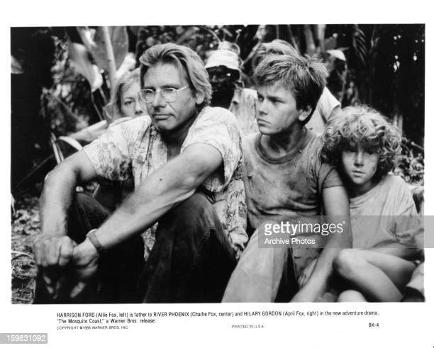 Harrison Ford and River Phoenix sitting in the jungle together in a scene from the film 'The Mosquito Coast' 1986