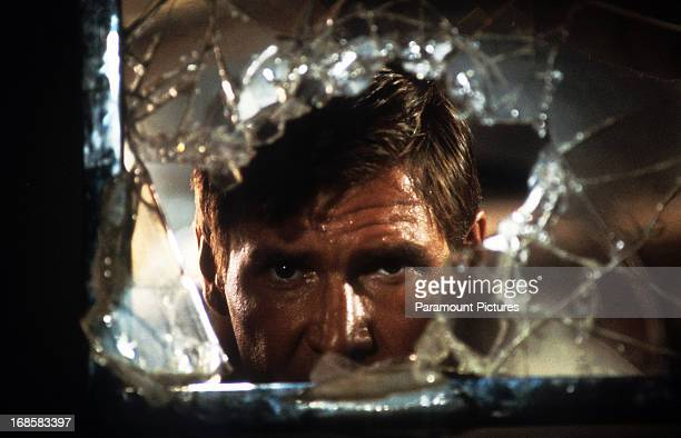 Harrison Ford looks through broken glass in a scene from the film 'Indiana Jones And The Temple Of Doom' 1984