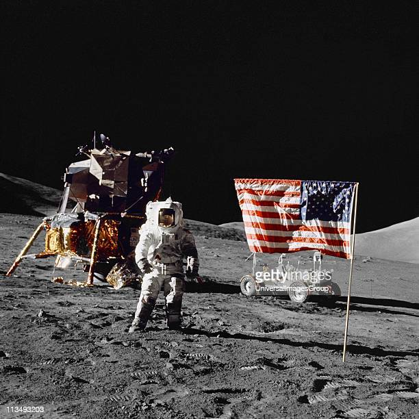 Harrison H Schmitt pilot of the lunar module stands on the lunar surface near the United States flag during NASA's final lunar landing mission in the...