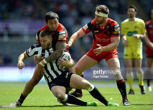 Harrison Hansen and Jordan Walne of Salford Red Devils challenge Ryhs Hanbury of Widnes Vikings during the Super League match between Salford Red...