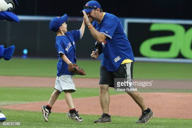 TORONTO ON AUGUST 9 Harrison Maye a 7yearold from PEI is a Hodgkin's Lymphoma survivor gets a high five from his father Cory after throwing out the...