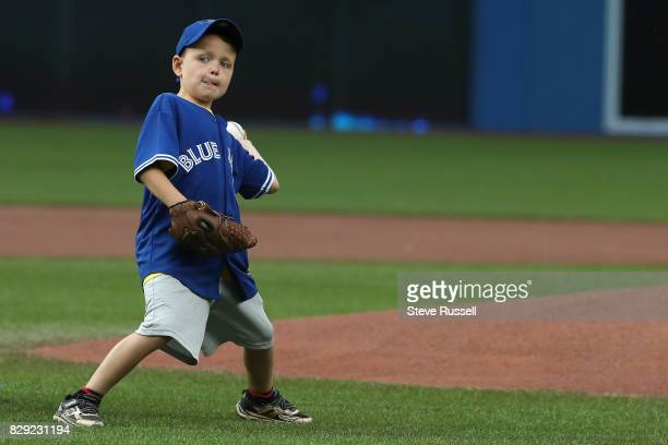 TORONTO ON AUGUST 9 Harrison Maye a 7yearold from PEI is a Hodgkin's Lymphoma survivor throws out the ceremonial first pitch as the Toronto Blue Jays...