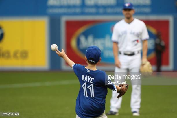 TORONTO ON AUGUST 9 Harrison Maye a 7yearold from PEI is a Hodgkin's Lymphoma survivor warms up with Toronto Blue Jays relief pitcher Taylor Cole...