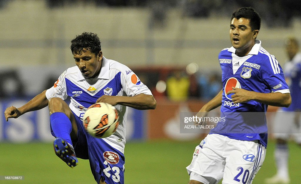 Harrison Otalvaro (R) of Colombia´s Millonarios vies for the ball with Abdon Reyes (L) of Bolivia's San Jose during their Copa Libertadores football match at Jesus Bermudez stadium in Oruro, Bolivia, on March 14, 2013.AFP PHOTO/Aizar Raldes