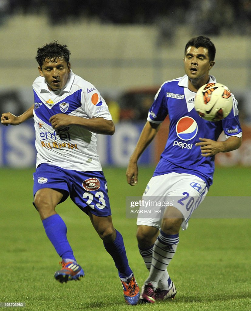 Harrison Otalvaro (R) of Colombia´s Millonarios vies for the ball with Abdon Reyes (L) of Bolivia's San Jose during their Copa Libertadores football match at Jesus Bermudez stadium in Oruro, Bolivia, on March 14, 2013. AFP PHOTO/Aizar Raldes