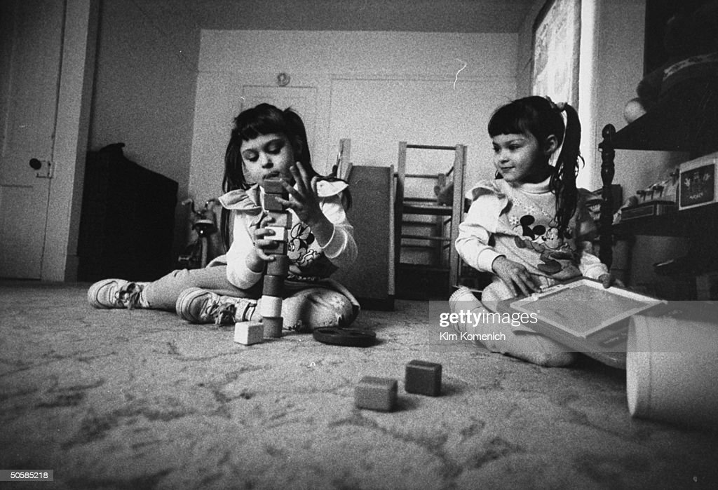 Harrison sisters Jaime Sherry playing w blocks on floor in their darkened room at home they are victims of a potentially fatal rare genetic skin...
